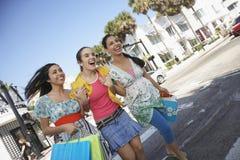 Tonårs- flickor med shoppingpåsar som korsar gatan Royaltyfria Bilder
