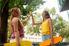 Tonårs- flickor med skateboarder som gör höjdpunkt fem Royaltyfri Fotografi