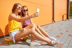 Tonårs- flickor med skateboarder som tar selfie Royaltyfri Bild