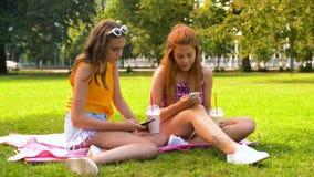 Tonårs- flickor med smartphones och skakor parkerar in stock video