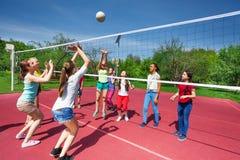 Tonårs- flickor och pojken spelar tillsammans volleyboll Arkivfoto
