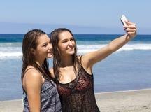 Tonårs- flickor på stranden som tar en Selfie Arkivbild