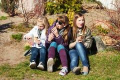 Tonårs- flickor som äter en glass Arkivbilder