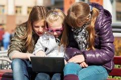 Tonårs- flickor som använder bärbara datorn på bänken Fotografering för Bildbyråer