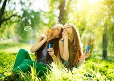 Tonårs- flickor som blåser såpbubblor arkivbild