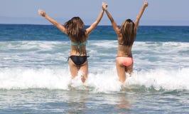 Tonårs- flickor som går in i havet på stranden Royaltyfri Fotografi