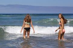 Tonårs- flickor som går in i havet på stranden Royaltyfria Foton