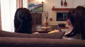 Tonårs- flickor som håller ögonen på tv och hemma kopplar av stock video
