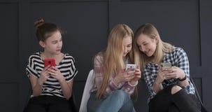 Tonårs- flickor som har gyckel medan textmessaging på mobiltelefoner lager videofilmer