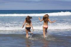 Tonårs- flickor som kör in i havet på stranden Arkivbilder