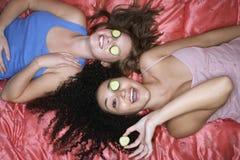Tonårs- flickor som ligger med gurkor över ögon royaltyfri foto