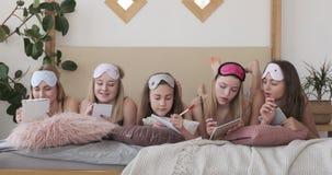 Tonårs- flickor som ligger på säng som skriver shoppinglistan i notepad lager videofilmer