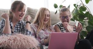 Tonårs- flickor som mottar goda nyheter på bärbara datorn arkivfilmer