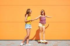 Tonårs- flickor som rider skateboarden på stadsgatan Arkivbild
