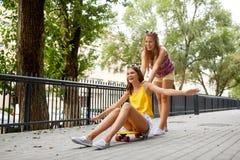 Tonårs- flickor som rider skateboarden på stadsgatan Arkivfoto