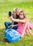Tonårs- flickor som sitter på gräs och tar selfie Royaltyfri Fotografi