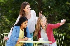 Tonårs- flickor som tar fotoet på mobiltelefonen på det utomhus- kafét royaltyfria bilder