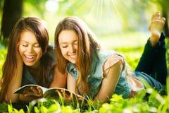 Tonårs- flickor som utomhus läser en tidskrift Royaltyfri Foto