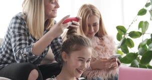 Tonårs- flickor upptagna användande bärbar dator och mobiltelefoner hemma lager videofilmer
