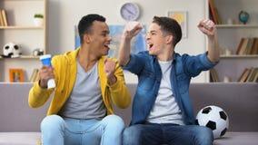 Tonårs- fotbollfans som hurrar för hemmastadd blåsa vuvuzela för nationellt fotbollslag lager videofilmer
