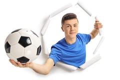 Tonårs- fotbollspelare som bryter till och med papper arkivbilder