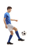 Tonårs- fotbollspelare som jonglerar en fotboll Arkivfoto