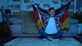 Tonårs- högskolestudent med den tyska flaggan som hurrar för nationellt fotbollslag arkivfilmer