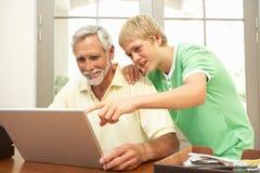 tonårs- hjälpande bärbar dator för farfarsonson att använda Royaltyfria Bilder