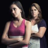 Tonårs- ilskna flicka och hennes moder som är ledsna och Fotografering för Bildbyråer