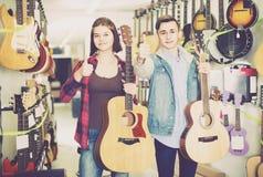 Tonårs- kunder som avgör på den passande akustiska gitarren i gitarr Arkivbild