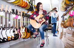 Tonårs- kunder som avgör på den passande akustiska gitarren i gitarr Arkivbilder