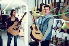 Tonårs- kunder som avgör på den passande akustiska gitarren i gitarr Fotografering för Bildbyråer