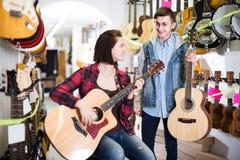 Tonårs- kunder som avgör på den passande akustiska gitarren i gitarr Royaltyfria Foton