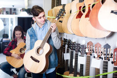 Tonårs- kunder som avgör på den passande akustiska gitarren i gitarr Royaltyfri Foto