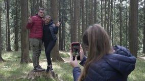 Tonårs- kvinna som tar foto med hennes smartphonekamera till ett ungt par som fotvandrar i träna - stock video