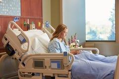 Tonårs- kvinnlig patient i sjukhussäng genom att använda mobiltelefonen arkivbilder
