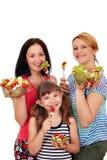 Tonårs- kvinnor och lilla flickan äter sallad fotografering för bildbyråer