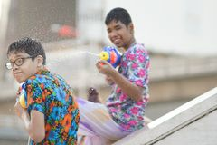 Tonårs- lekvatten med hans vän under Songkran Royaltyfria Bilder