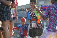 Tonårs- lekvatten med hans vänner under Songkran Arkivfoton
