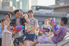 Tonårs- lekvatten med hans vänner under Songkran Arkivbilder