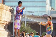 Tonårs- lekvatten med hans vänner under Songkran Royaltyfria Bilder