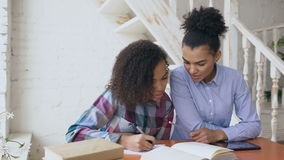 Tonårs- lockigt haired ung flickasammanträde för blandat lopp på fokuserat koncentrera för tabell lära kurser och hennes fläder stock video