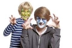 Tonårs- och unga pojkar med vänder mot den målningmonster och wolfen Arkivfoto