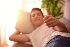 Tonårs- på en soffa hemma som gör det ok tecknet arkivbilder