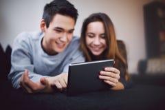 Tonårs- par genom att använda den digitala minnestavlan - inomhus Arkivfoto