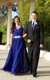 Tonårs- par som går till studentbalen som går och ler Arkivfoto