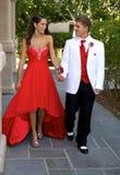 Tonårs- par som går till studentbalen som går och ler på de royaltyfria bilder