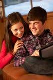Tonårs- par som kopplar av på sofaen med bärbar dator Arkivbild