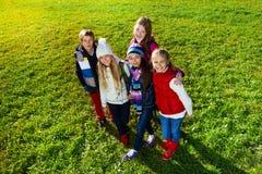 Tonårs- pojkar och flickor på gräsmattan Royaltyfri Bild