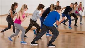 Tonårs- pojkar och flickor som lär i dansställe Arkivfoto